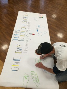 Student signing traced foot (photo provided by Katelyn Clark)