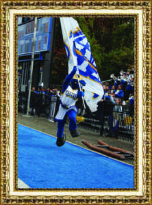 """Gabby Pericone, Senior Charlie the Charger North Campus Saturday, Oct. 23, 2015 """"Charlie the Charger ecstatically runs with the UNH flag after one of many Homecoming Game touchdowns."""""""